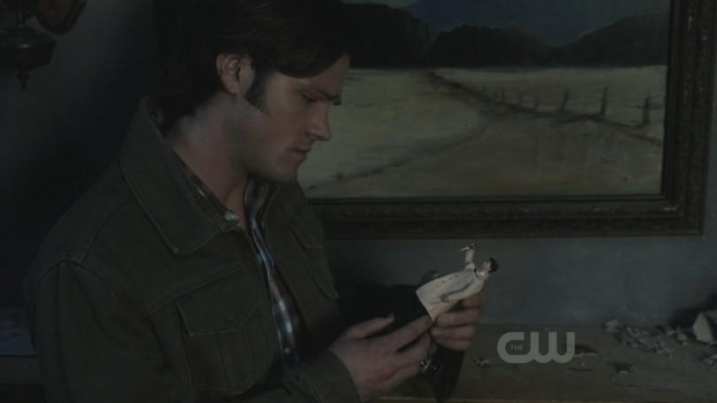 站在璧爐前把玩 Castiel 娃娃的 Sam